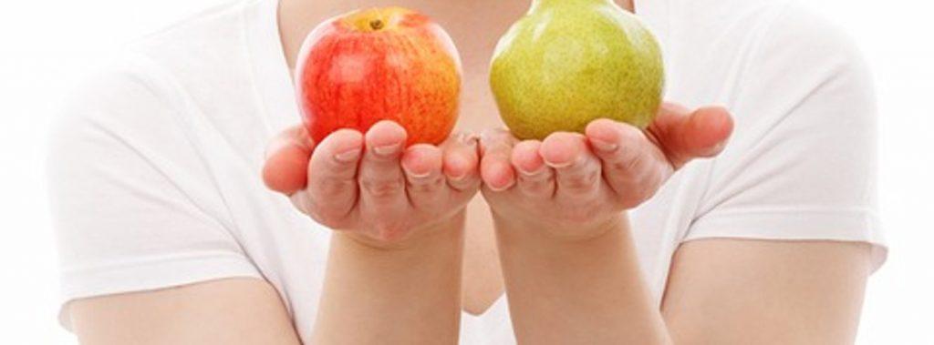 kobieta trzymająca jabłko i gruszkę